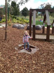 Lillian in dinosaur footprint