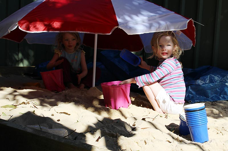 The girls add a beach umbrella