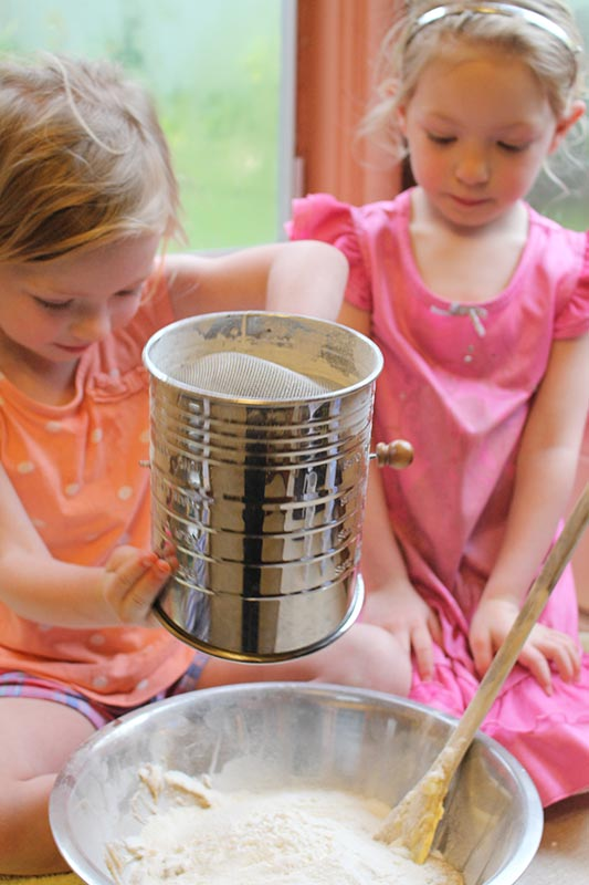 The girls helping prepare the ingredients & sifting flour