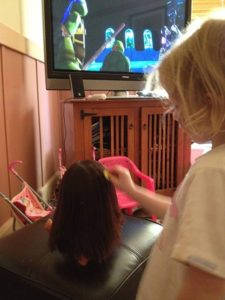 Making sure Dora's hair is brushed, while watching the Teenage Mutant Ninja Turtles