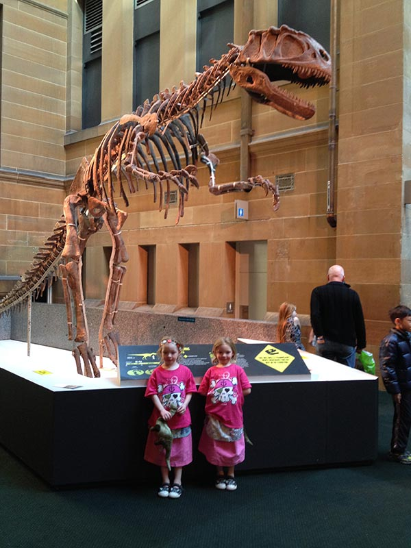 The girls at one of the skeleton remains of a dinosaur.