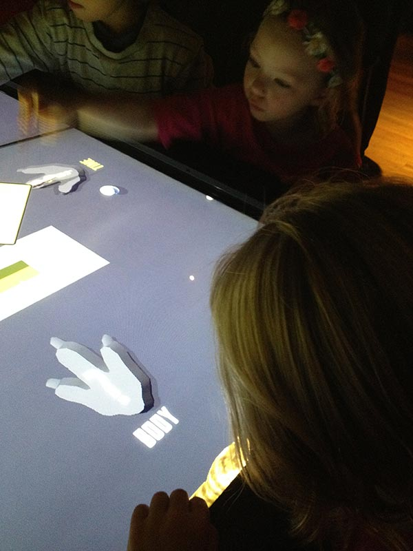 The girls playing with the touch screen.
