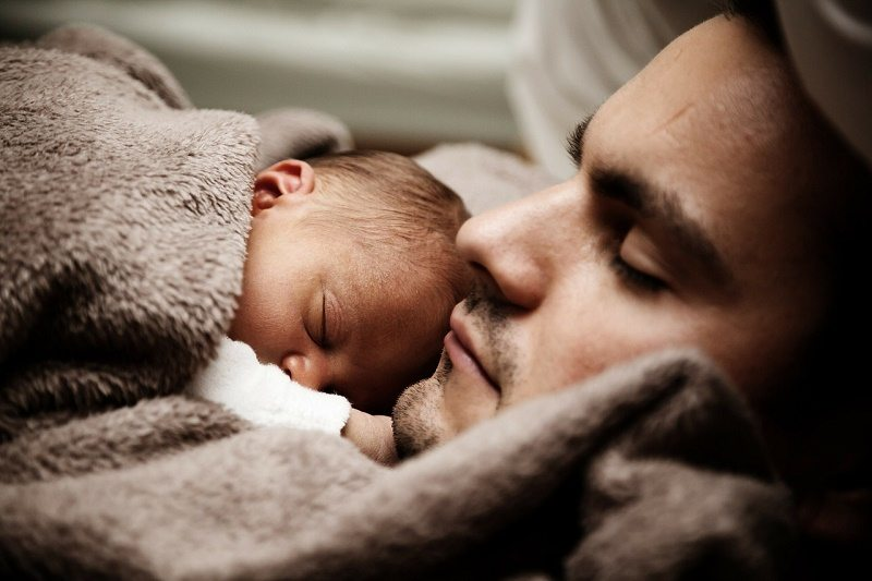 A father with his new little baby. Finally sleeping. Now not to move!