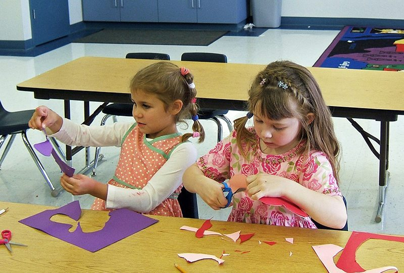 Children learning how to cut out shapes and to use in craft projects.