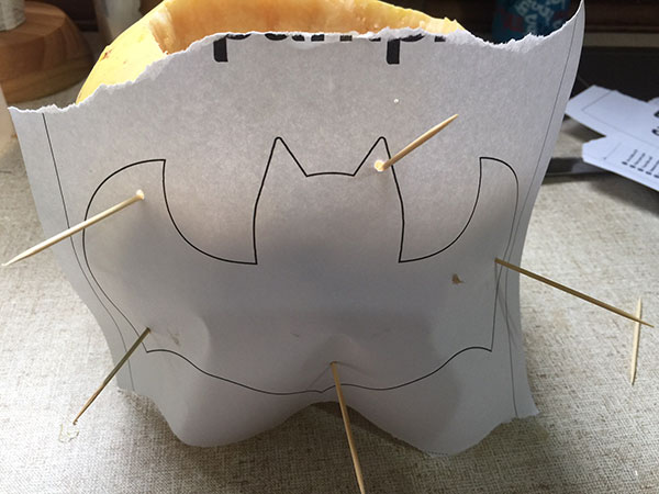 Now the stencil is attached to the pumpkin you can use the knife to mark the lines of the bat. Once you have all the lines there you can remove the stencil and start to create the bat.