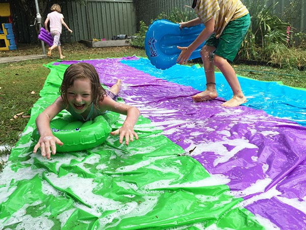 The kids having a great time with the triple Superslide from Clark Rubber.