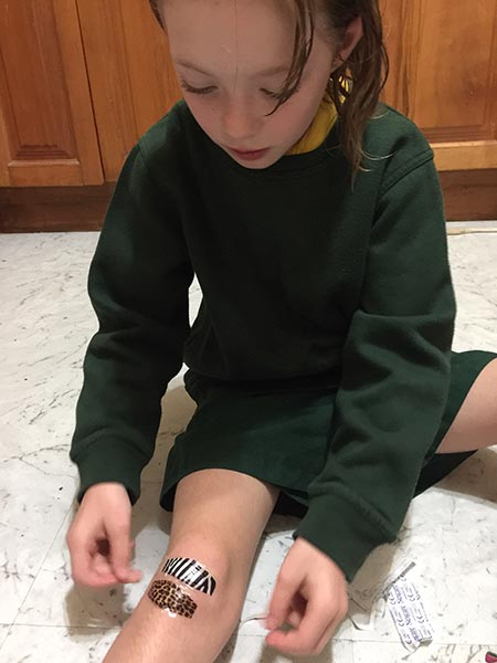 Julia putting on some Nexcare Animal Print Waterproof Bandages. The girls love the animal prints and think they look wonderful on. After the bandage is on the scraped knee and leg is all forgotten about.