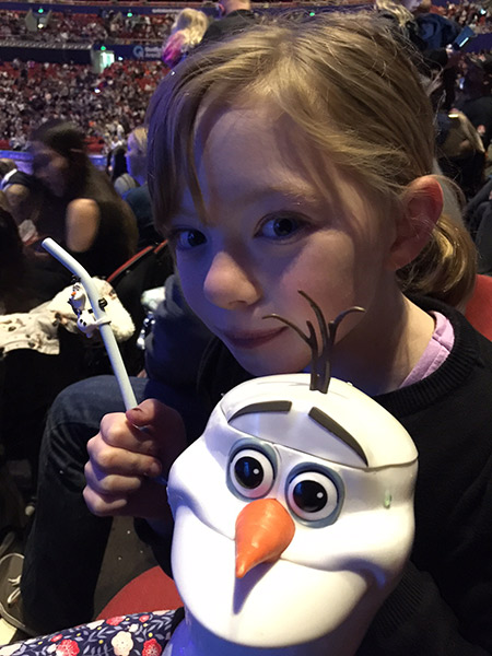 Julia with her Olaf cup and waiting for the show to start.