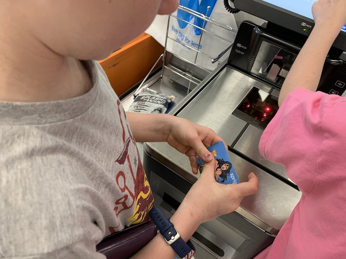 Lillian shopping for some fun things with her Spriggy Wonder Woman Pre-Paid Debit Card.