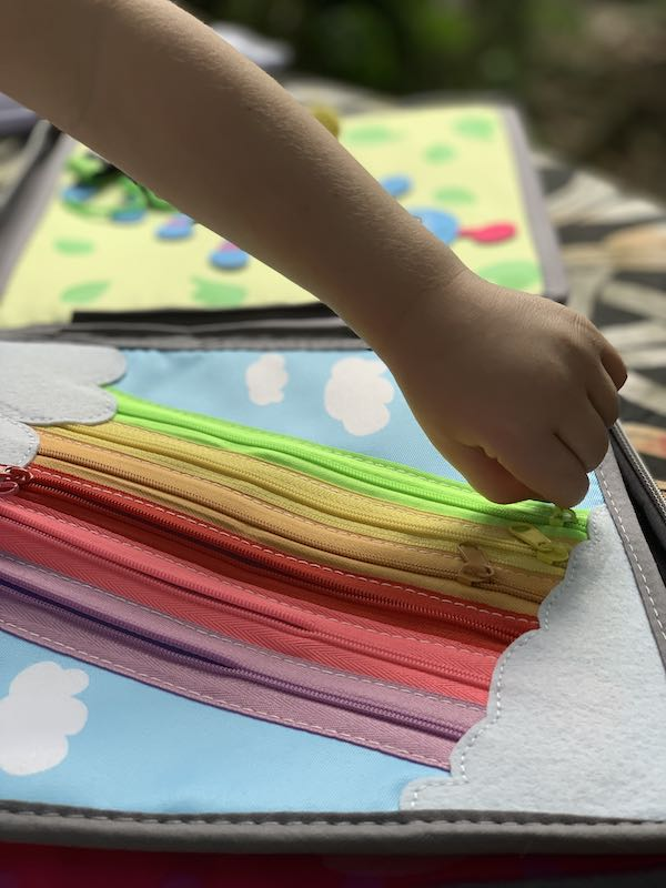 Having fun with the rainbow zippers - Kids can open and close them, this helps with their fine motor skills.